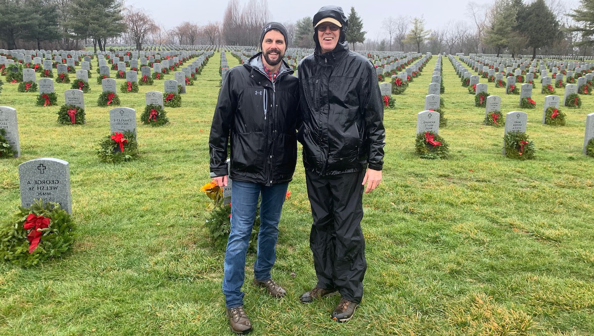 凯文·墨菲 and his dad standing in front of a cemetery with freshly laid wreaths